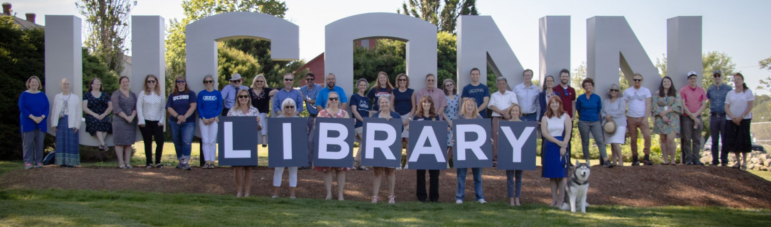 UConn Library staff in front of UConn Sign