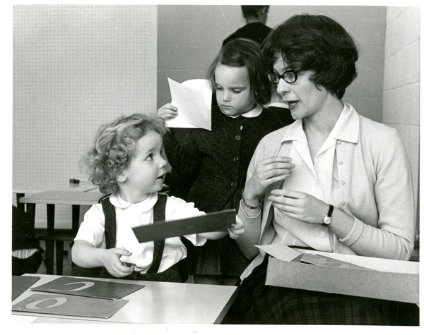 Photograph of a child using sandpaper letter while looking at teacher. Other students work in the background.