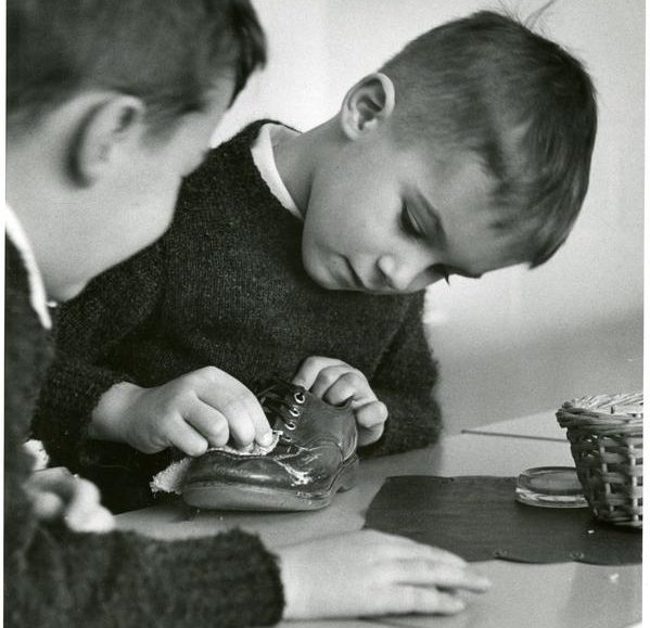 A student at Whitby polishes a shoe while his classmate observes
