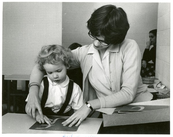 A teacher helps a child trace a letter with her finger.