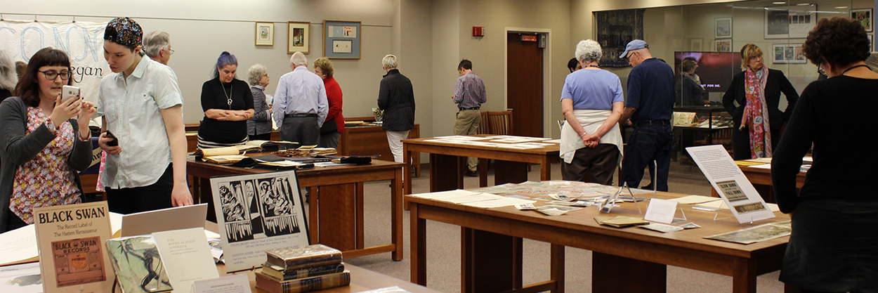 Photo of event in Archives & Special Collections reading room, people looking at collection materials