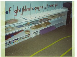A photograph of educational materials stored on low shelves that are accessible to students.