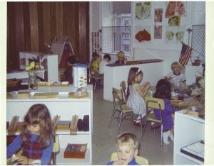A photograph of children sitting in child-sized chairs and child-sized tables in a classroom.