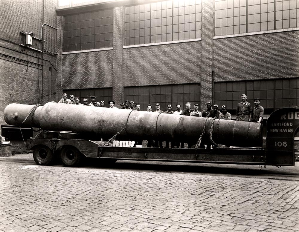 Photo from Archives & Special Collections Business Collections, line of men standing behind a large beam on a truck bed in front of a factory-like building.